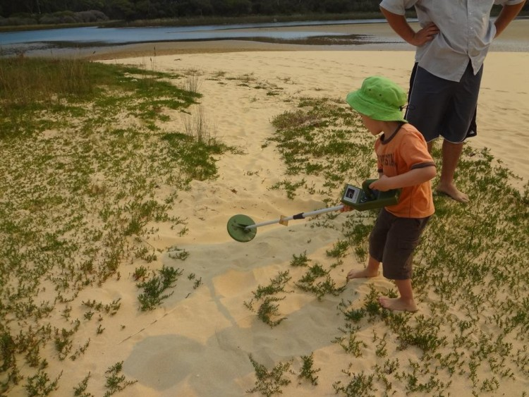Kids Activities: The boy use metal detector to find a treasure